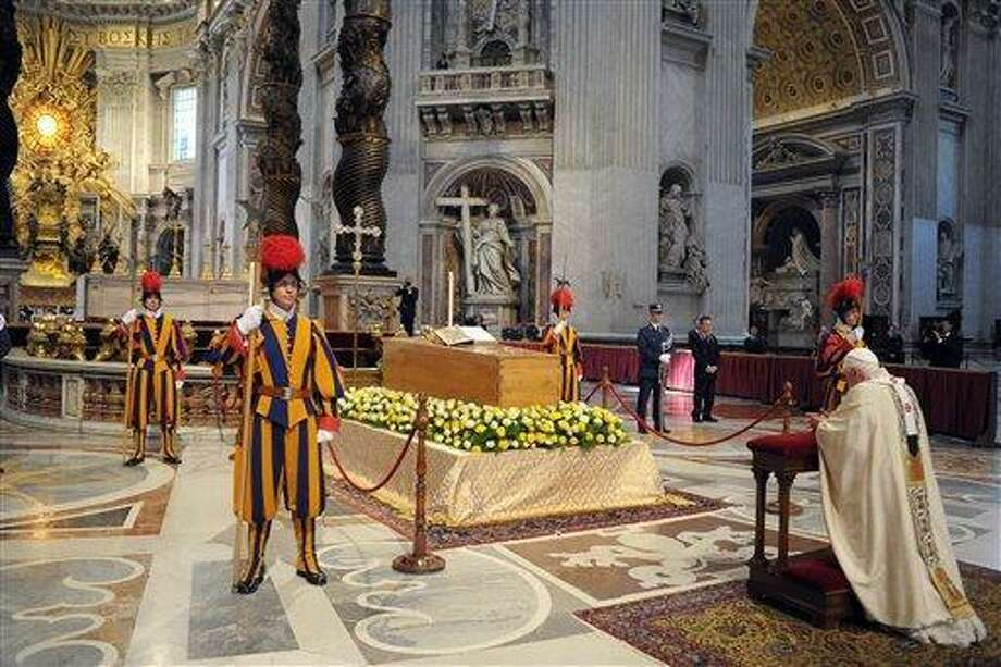 In this photo provided by the Vatican newspaper L'Osservatore Romano, Pope Benedict XVI kneels in prayer in front of the casket of late Pope John Paul II, laid out in state at the Altar of the Confession inside St. Peter's Basilica, at the Vatican, Sunday, May 1, 2011. Pope Benedict XVI beatified Pope John Paul II before more than a million faithful in St. Peter's Square and surrounding streets Sunday, moving the beloved former pontiff one step closer to possible sainthood. (AP Photo/L'Osservatore Romano, ho) Photo: AP / L'Osservatore Romano
