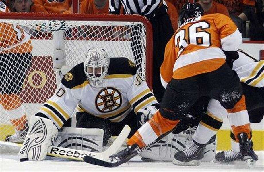 Boston Bruins goalie Tim Thomas, left, blocks a shot by Philadelphia Flyers' Darroll Powe during the first period in Game 1 of the Eastern Conference semifinal NHL Stanley Cup playoffs series, Saturday, April 30, 2011, in Philadelphia. (AP Photo/Matt Slocum) Photo: AP / AP