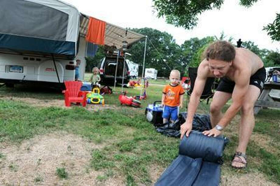 Patrick Mosur of New Britain, 2, watches his father Piotr Mosur roll up an air mattress as they pack up Friday during an evacuation of the campground at  Hammonasett State Park in Madison because of expected high winds from Hurricane Earl.  Peter Hvizdak / Journal Register News
