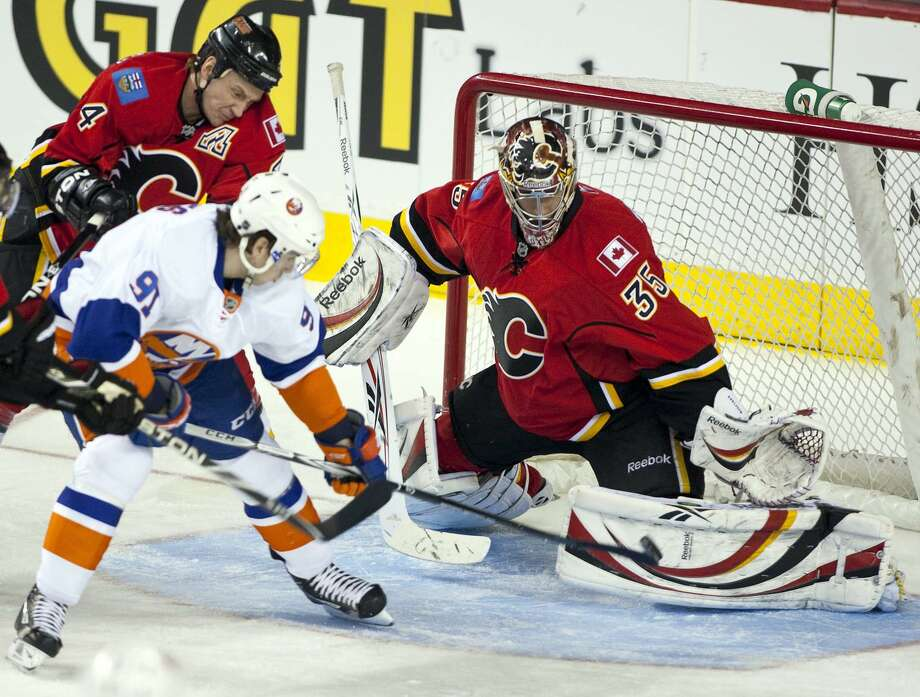 New York Islanders' John Tavares, center, lifts the puck past Calgary Flames goalie Henrik Karlsson, right, from Sweden, as Jay Bouwmeester tries to stop him during first period NHL hockey action in Calgary, Canada, Monday, Jan. 3, 2011. (AP Photo/The Canadian Press, Jeff McIntosh) / THE CANADIAN PRESS