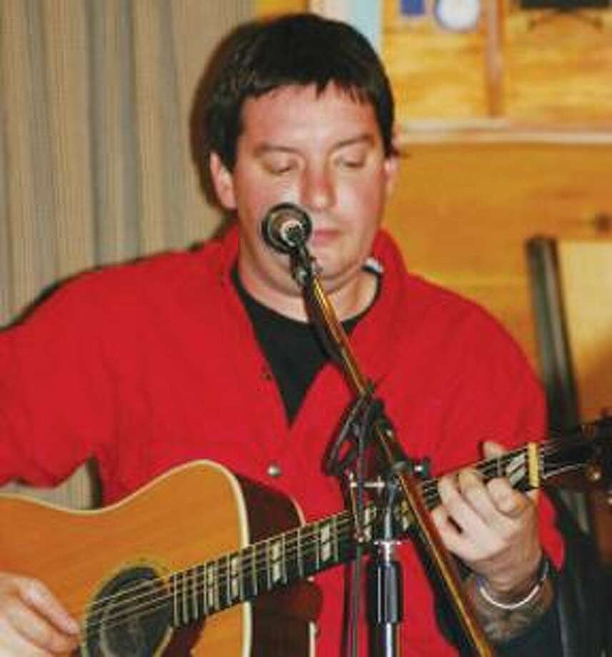 "Travis Moody is seen playing the acoustic guitar. Friends will gather for the ""Blues for Moody"" benefit to help cover medical and other expenses after a workplace accident involving Moody occured Sunday at Cafe Nine. (Domenic Forcella)"