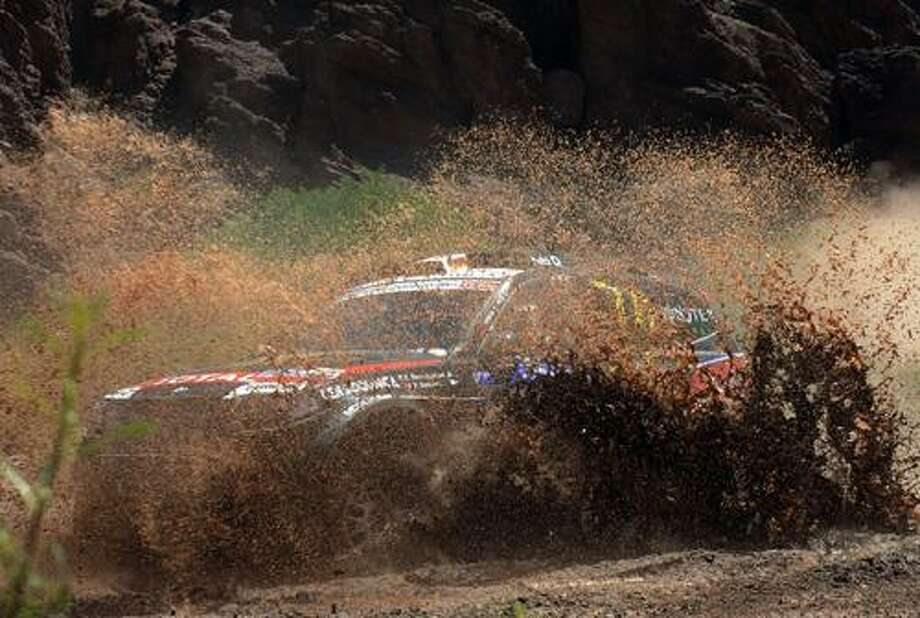 AP Photo/Daniel Garcia, Pool BMW car driver Stephane Peterhansel and co-driver Jean-paul Cottret of France competes in the third stage of the 2011 Argentina-Chile Dakar Rally between San Miguel de Tucuman and Jujuy, Argentina, Tuesday.