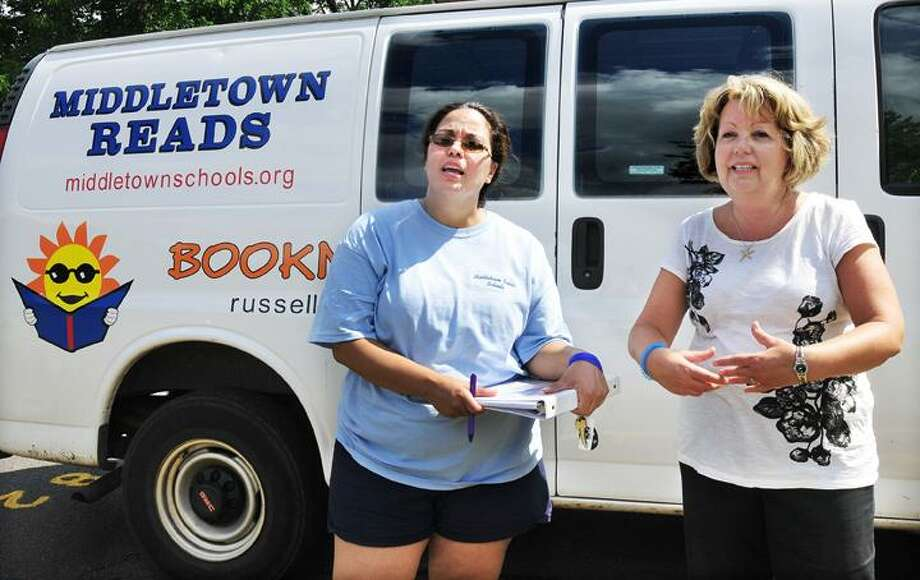 "The Middletown Press  6.29.11  Volunteer Victoria Alderman, 17, a rising senior at Middletown High School helps distribute free books to Plaza Drive residents Jonathan Haouchine, 9 and Alexa Rodriguez, 7 from the Middletown Schools Bookmobile Wednesday afternoon. To buy a print of this photo and more, visit <a href=""http://www.middletownpress.com"">www.middletownpress.com</a> / TheMiddletownPress"