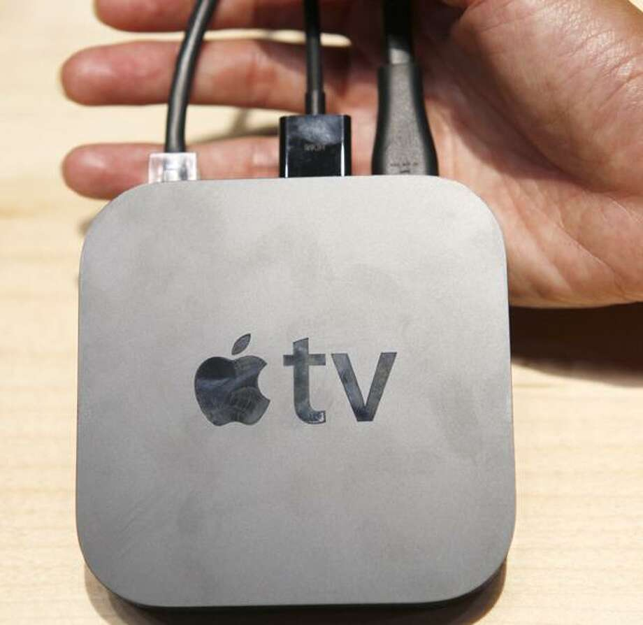 An Apple employee holds a new Apple TV device, Wednesday, Sept. 1, 2010, during a news conference in San Francisco. Apple Inc. announced a smaller, cheaper version of its Apple TV device for streaming movies and television shows over the Internet and into the living room. It also unveiled a new line of iPods, including a touch-screen Nano model. (AP Photo/Paul Sakuma) Photo: ASSOCIATED PRESS / AP