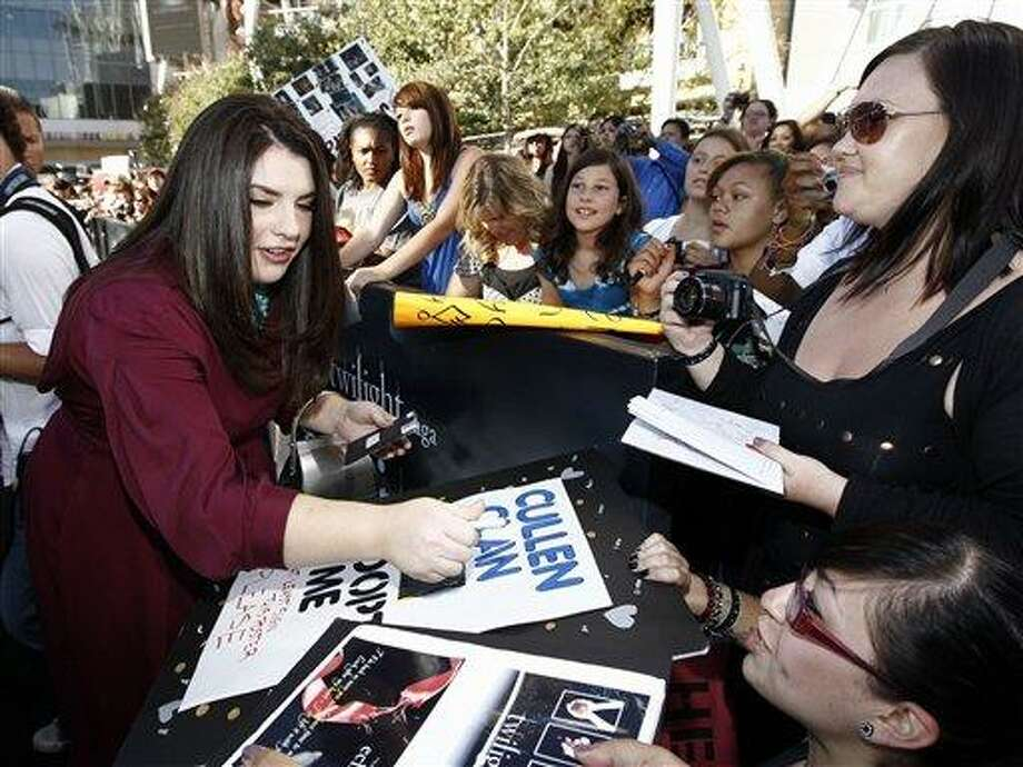 """Stephenie Meyer signs autographs as she arrives at the premiere of """"The Twilight Saga: Eclipse"""" on June 24 in Los Angeles. (AP) Photo: ASSOCIATED PRESS / AP"""