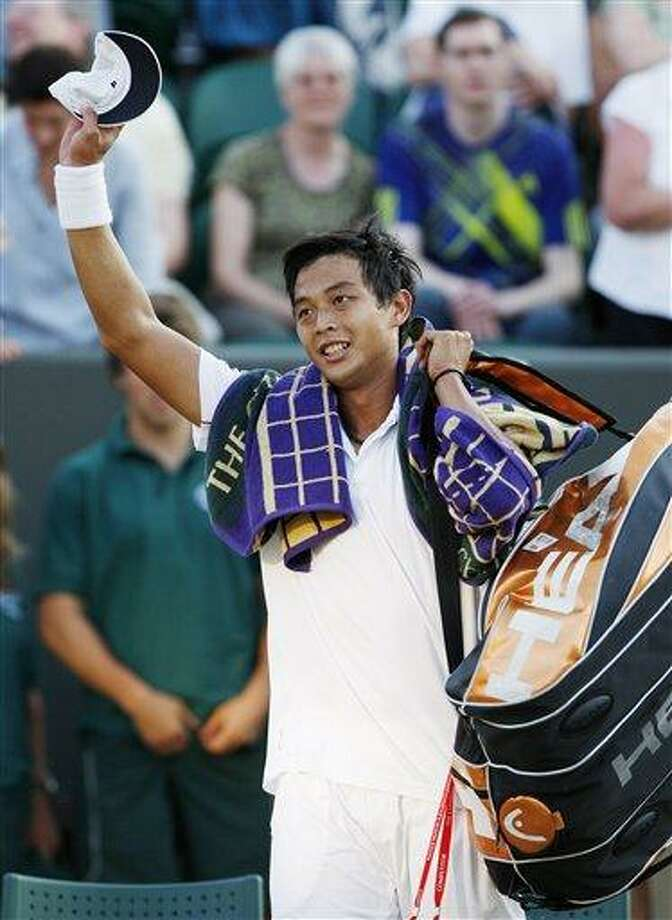 Taiwan's Lu Yen-Hsun waves to the crowd as he celebrates his win over Andy Roddick of the U.S. at the All England Lawn Tennis Championships at Wimbledon, Monday. (AP) Photo: ASSOCIATED PRESS / AP