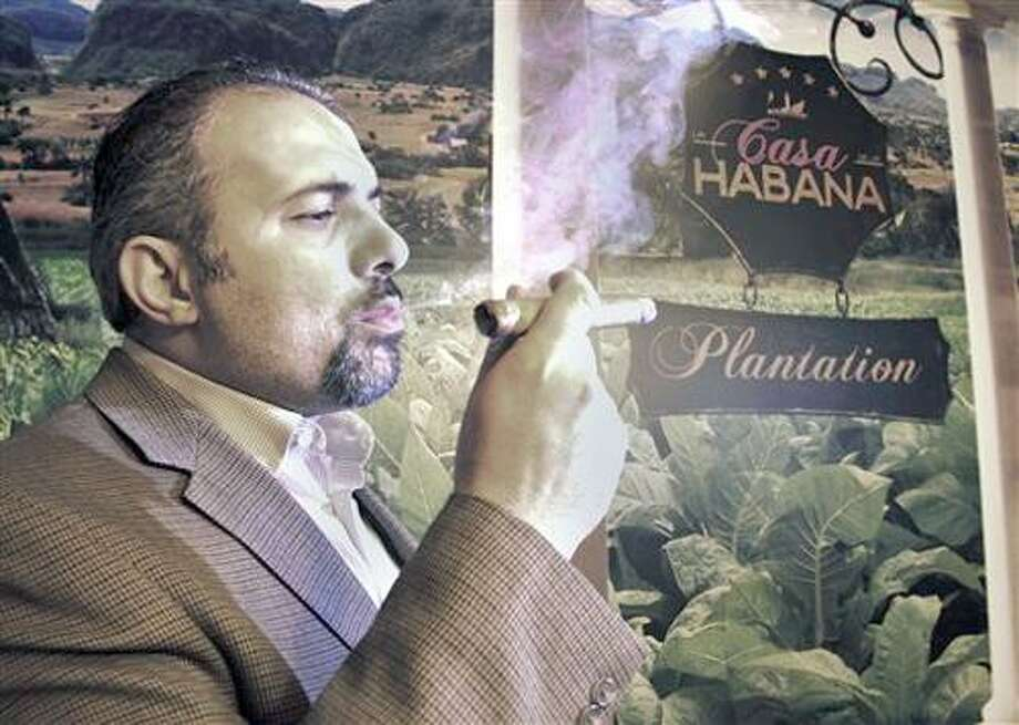 Ismail Houmani, founder and director of La Casa De La Habana, enjoys a cigar at his establishment on Wednesday, Dec. 22, 2010 in Detroit. Cuba's government-controlled tobacco company is suing the owner of cigar shops in the Detroit area, claiming his business' name is too similar to its own global franchise. Houmani owns four cigar lounges called La Casa De La Habana, in Detroit, Plymouth, Mich., Ann Arbor, Mich., and Toledo, Ohio. Cubatabaco's stores are named La Casa del Habano. Cuba can't do business in America because of a nearly 50-year-old trade embargo. Nonetheless, Cubatabaco claims it still has a right to protect its U.S. trademark.  (AP Photo/Jerry S. Mendoza) Photo: AP / FR88721 AP