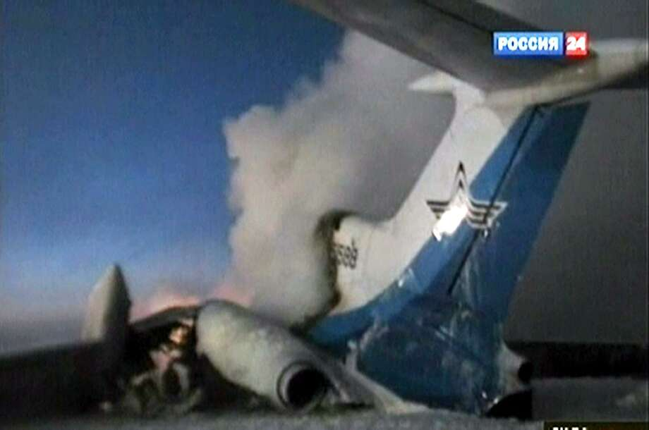 In this image taken from Russia 24 television channel TV, showing a tail part of the Russian passenger Tu-154 aircraft seen after an explosion in Surgut, about 2200 kilometers (1,350 miles) east of Moscow, Russia, Saturday, Jan. 1, 2011. The Russian passenger jet carrying 128 people caught fire and later exploded at a Siberian airport on Saturday, killing one person and injuring several others, officials said.  The rest of the passengers and crew were safely evacuated before the explosion in the Western Siberian oil town of Surgut. (AP Photo/Rossia 24 Television Channel) Photo: ASSOCIATED PRESS / AP2011