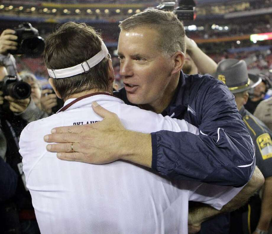 AP Connecticut head coach Randy Edsall, right, embraces Oklahoma head coach Bob Stoops after Oklahoma defeated Connecticut in the Fiesta Bowl, Saturday, in Glendale, Ariz. Oklahoma won 48-20. Edsall is slated to become the next head coach at the University of Maryland.
