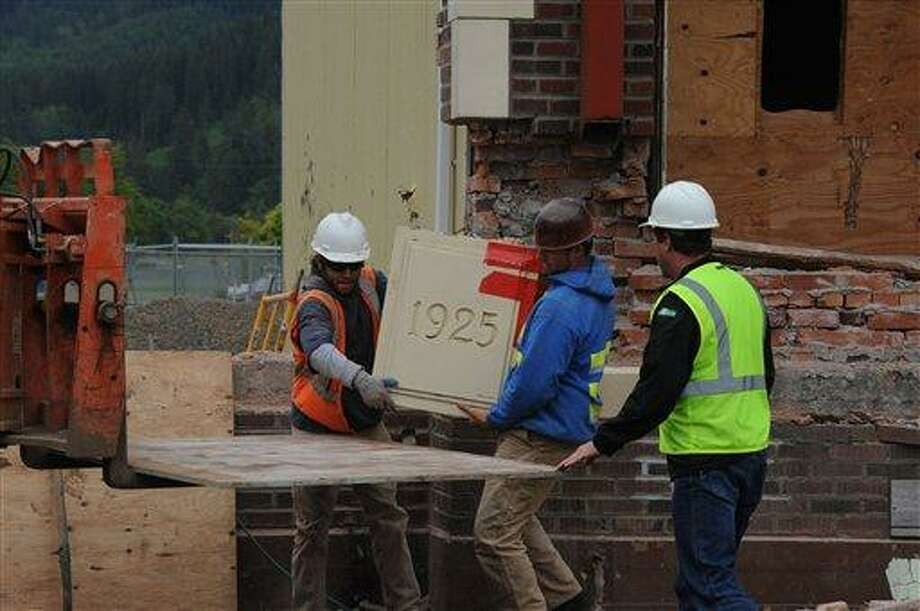 In a June 16, photo construction workers, watched by Bill Henderson, right, Quillayute Valley School District maintenance supervisor, remove the cornerstone from the 1925 portion of the Forks High School in Forks, Wash. The condition of the 86-year-old brick-and-morter facade was too poor to save without expensive renovations. The high school became famous after it was used as a setting in the Twilight series of teen romance novels.  (AP Photo/Lonnie Archibald/Peninsula Daily News) Photo: AP / Peninsula Daily News