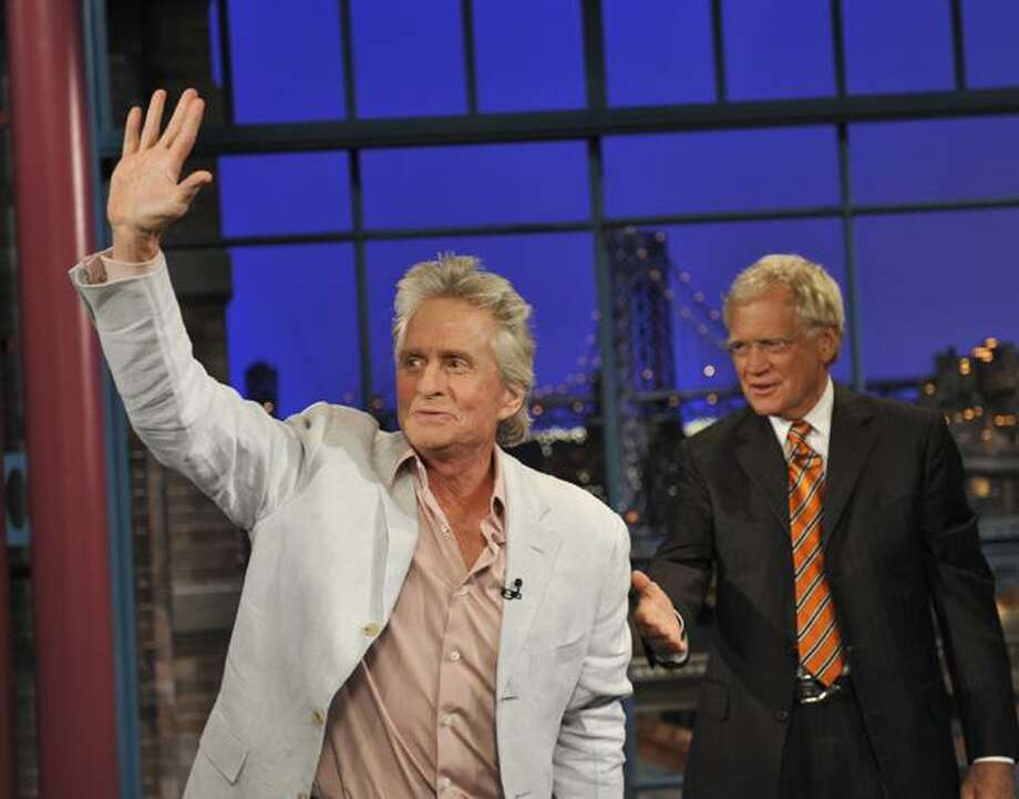 "In this photo provided by CBS, Michael Douglas waves to the Late Show audience after a hug from host David Letterman during the Tuesday, Aug. 31, 2010 taping of the show in New York. Douglas said he faces an ""eight-week struggle"" against throat cancer but is optimistic about his chances for recovery. (AP Photo/CBS, John Paul Filo) Photo: AP / CBS PHOTO by JOHN PAUL FILO. ©2010 CBS BROADCASTING INC. ALL RIGHTS RESERVED."
