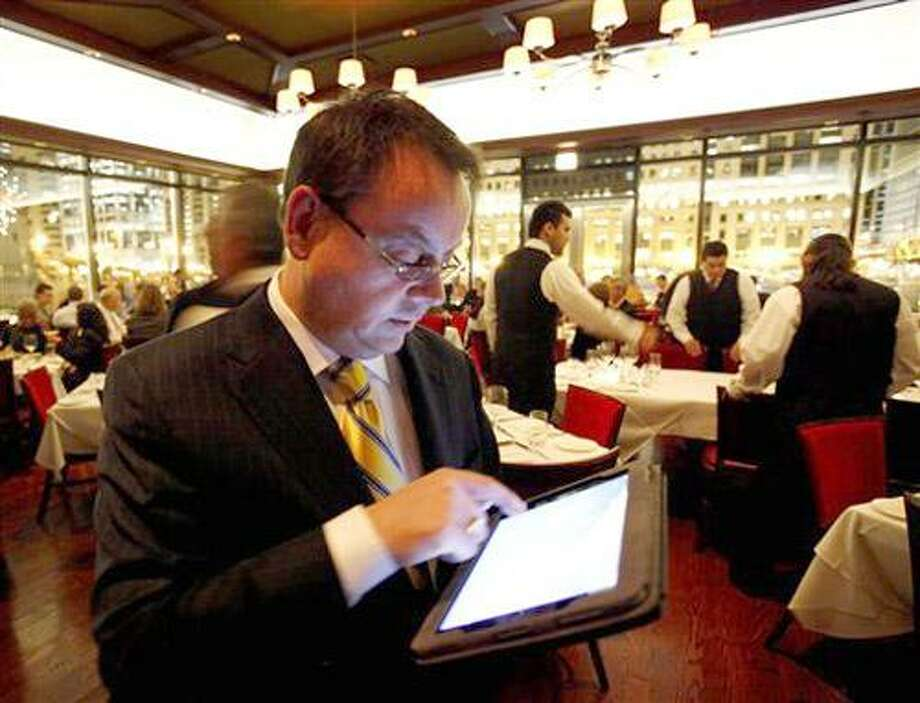 In this photo taken Wednesday, Dec. 1, 2010, Chicago Cut steakhouse managing partner Matt Moore browses the restaurant's wine list on an iPad in Chicago. The restaurant is just one eatery of several across the U.S. that have started uploading menus and wine lists to the digital devices.     (AP Photo/Charles Rex Arbogast) Photo: AP / AP