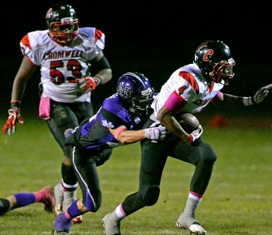 Cromwell running back Derrick Villard runs for a long gain after breaking a tackle from North Branford linebacker Gary Falanga. Photo by Sean Meenaghan/New Haven Register.