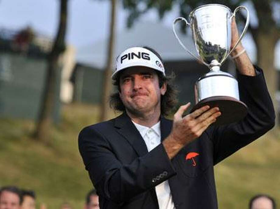 Bubba Watson holds up the championship trophy at the Travelers Championship golf tournament on Sunday. (AP) Photo: ASSOCIATED PRESS / FR125654 AP