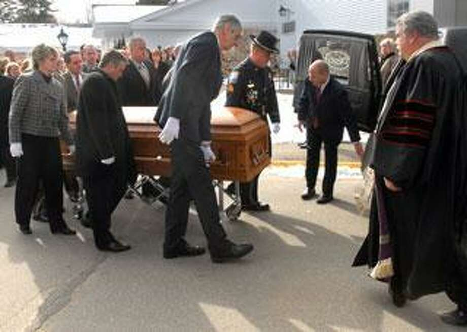 The casket of Raymond Dobratz is placed in a hearse outside the First Church of Christ Congregational in Old Saybrook surrounded by family and friends. Dobratz was killed in the Middletown gas plant explosion. (Mara Lavitt/Register)