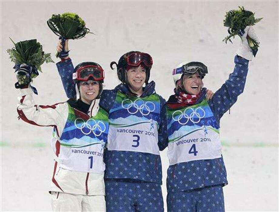Olympic champion in women's moguls Hannah Kearney of the USA, center, runner up Jennifer Heil of Canada, left and third placed Shannon Bahrke of the USA, right pose a the podium during a flower ceremony at the Vancouver 2010 Olympics in Vancouver, British Columbia, Saturday, Feb. 13, 2010. (AP Photo/Jae C. Hong) Photo: AP / AP