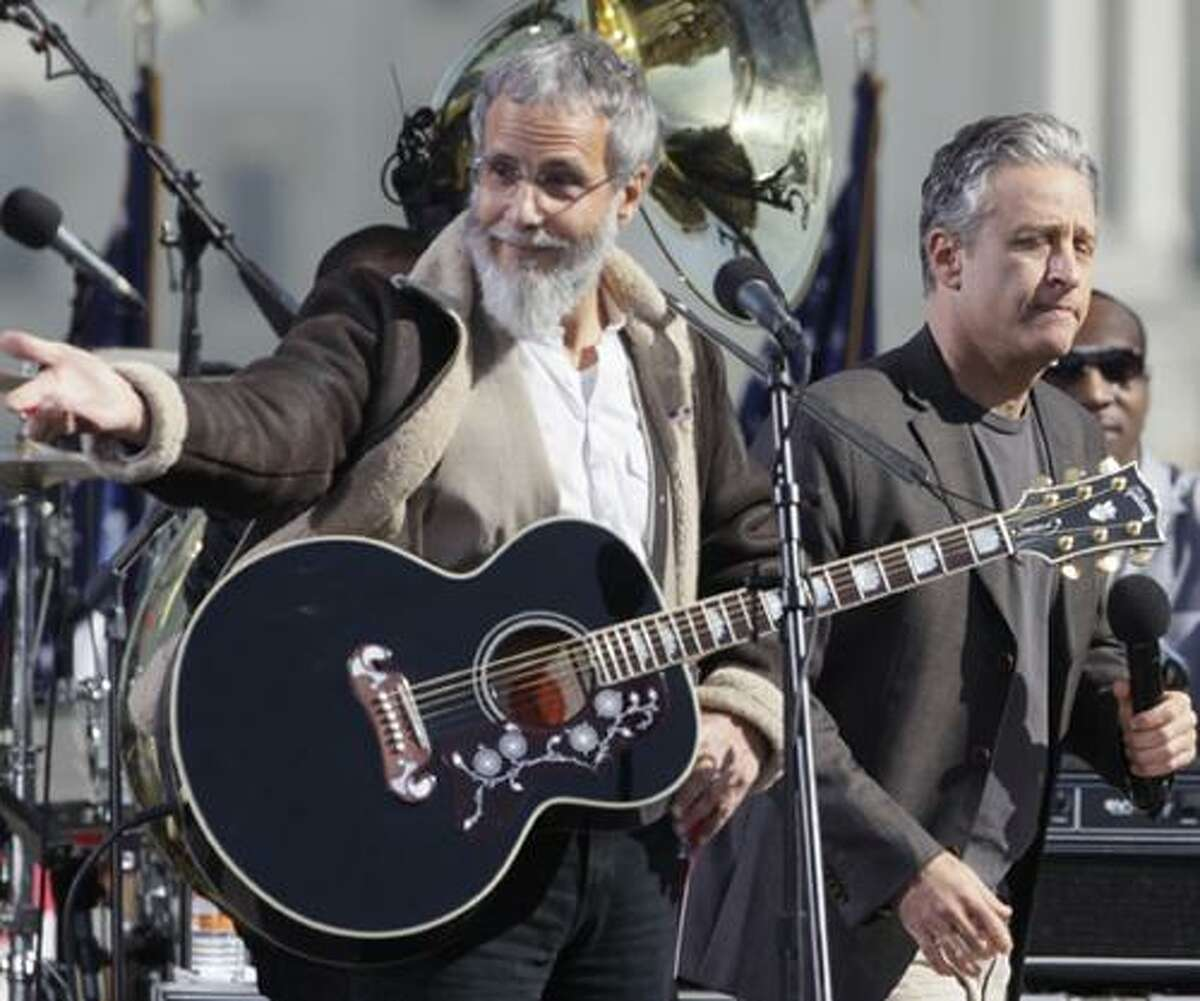 """Folk artist Yusuf (formerly Cat Stevens), left, and comedian Jon Stewart perform during the Rally to Restore Sanity and/or Fear on the National Mall in Washington, Saturday, Oct. 30, 2010. The """"sanity"""" rally blending laughs and political activism drew thousands to the mall with Stewart and comedian Stephen Colbert casting themselves as the unlikely maestros of moderation and civility in polarized times.(AP Photo/Carolyn Kaster)"""