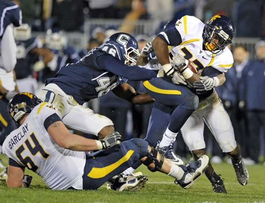 West Virginia's Ryan Clarke is tackled by Connecticut's Sio Moore, left, and Jerome Junior, background, during overtime in Connecticut's 16-13 victory in their NCAA football game in East Hartford, Conn., on Friday, Oct. 29, 2010. Clarke fumbled on the play and the ball was recovered by Connecticut, setting up their game winning drive. (AP Photo/Fred Beckham) Photo: AP / FR153656 AP