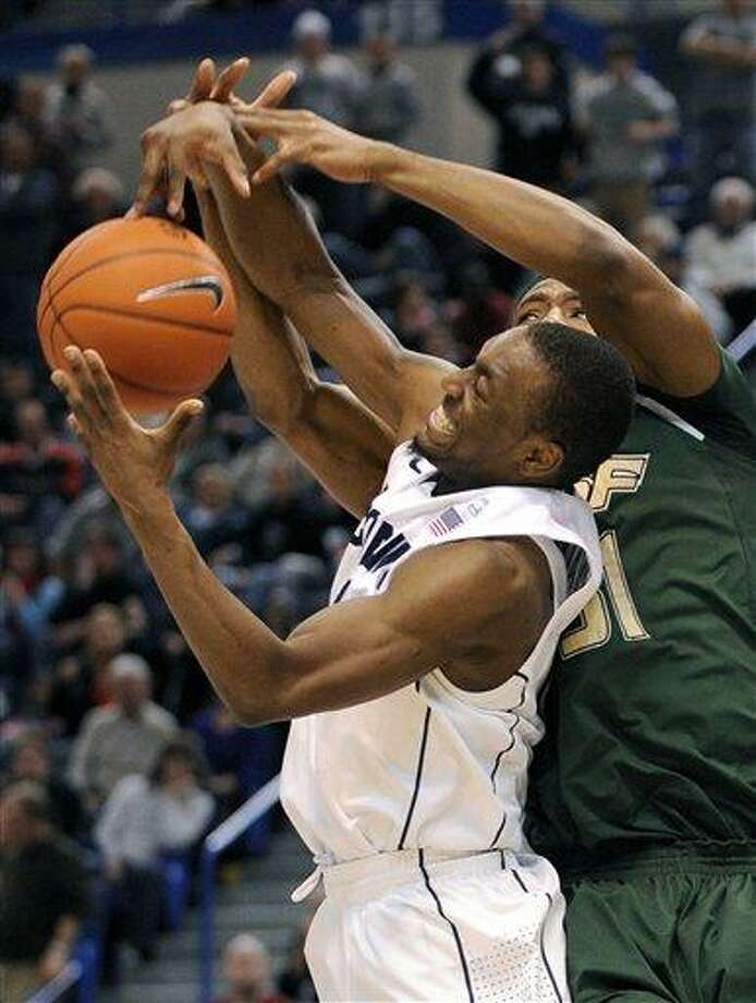 Connecticut's Kemba Walker, left, grabs a rebound from South Florida's Jarrid Famous during the second half of Connecticut's 66-61 overtime victory in an NCAA college basketball game in Hartford, Conn., on Friday, Dec. 31, 2010. Walker scored a game-high 24 points and had eight rebounds during the game. (AP Photo/Fred Beckham) Photo: AP / FR153656 AP