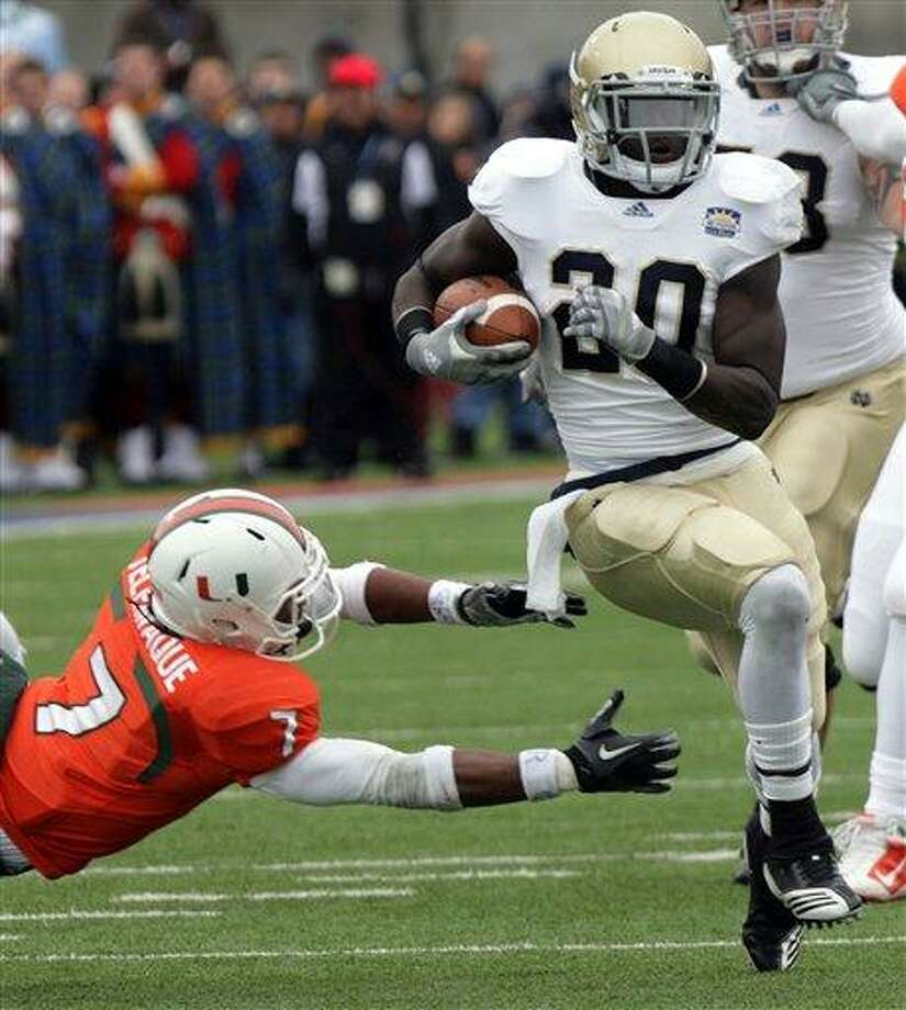 Notre Dame running back Cierre Wood, right, runs past Miami defensive back Vaughn Telemaque, left, on his way in to the end zone during the Sun Bowl NCAA college football game on Friday, Dec. 31, 2010, in El Paso, Texas. (AP Photo/El Paso Times, Mark Lambie) Photo: AP / El Paso Times