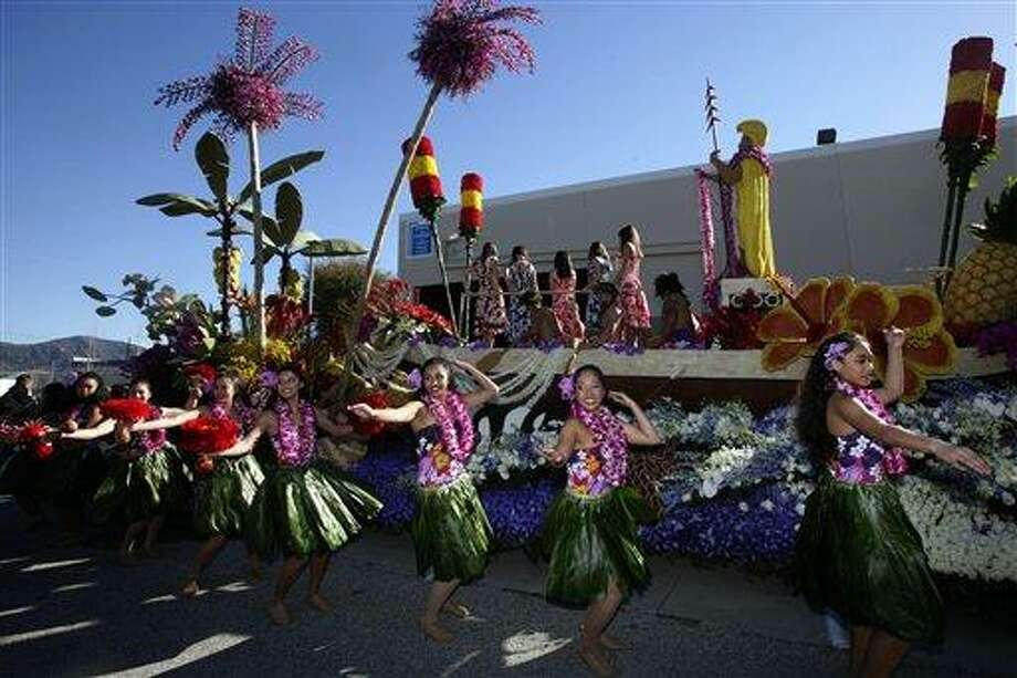 "Hawaiian dancers practice dancing and moving along with the Dole ""Living Well in Paradise"" rose float in Irwindale, Calif., Dec 31, 2010. Celebrating the 122 Annual Rose Bowl Parade held New Year's day in Pasadena, Calif. (AP Photo/Nick Ut) Photo: AP / AP"