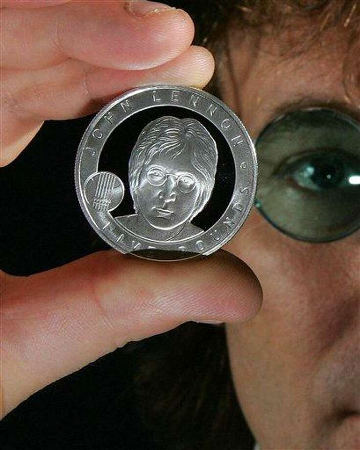 In this image dated Oct. 18, 2010, released by the British Royal Mint, showing John Lennon look-a-like Alan Swoffer, poses with the new John Lennon pound coin which goes on sale Friday Oct. 29, 2010.  The new coin depicting rock icon John Lennon who is being honored with an official British commemorative coin.  The former member of the Beatles singer songwriter Lennon was chosen by a public vote to be honoured with the coin with a face value of 5 pounds (US $ 8) but will be sold at 45 pounds (US $ 71.68) in a limited edition on sale Friday. The former Beatle will join William Shakespeare, Winston Churchill, Charles Darwin, Florence Nightingale among British luminaries whose images have graced special coins. (AP Photo/ Geoff Caddick, The Royal Mint) ** Editorial Use Only ** Photo: AP / Ho The British Royal Mint