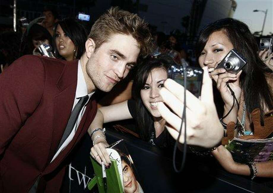 """Actor Robert Pattinson poses with fans at the premiere of """"The Twilight Saga: Eclipse"""" on Thursday, June 24, 2010 in Los Angeles.  (AP Photo/Matt Sayles) Photo: AP / AP"""