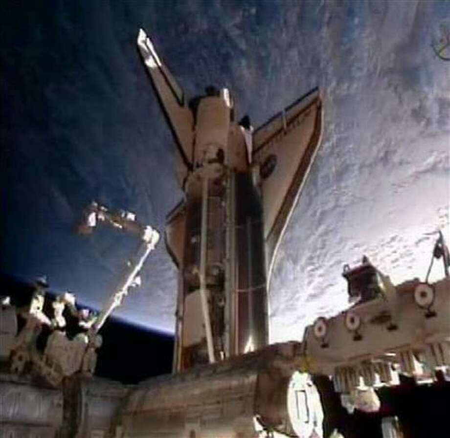 In this frame grab from video taken from NASA television, space shuttle Discovery is seen moments after docking at the International Space Station, its final visit before being parked at a museum, Saturday, Feb. 26, 2011. (AP Photo/NASA) Photo: ASSOCIATED PRESS / AP2011