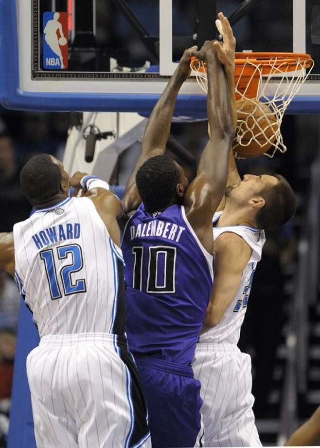 AP Sacramento Kings center Samuel Dalembert (10) dunks the ball between Orlando Magic center Dwight Howard, left, and Ryan Anderson, right, during the first half of an NBA basketball game in Orlando, Fla., Wednesday.