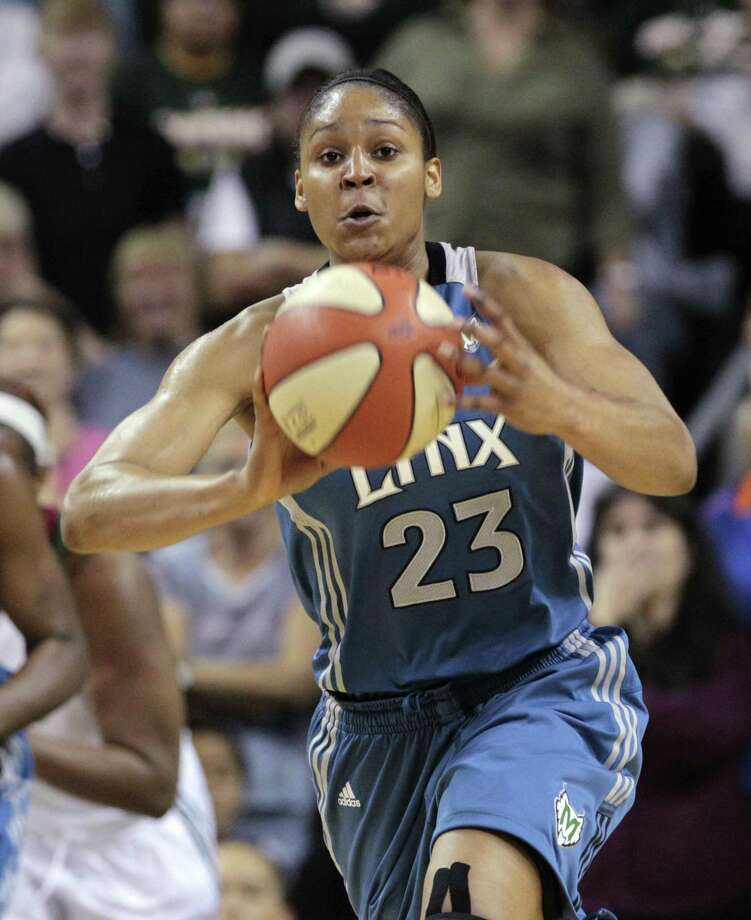 Minnesota Lynx's Maya Moore makes a pass on the run against the Seattle Storm in the first half of a WNBA basketball game, Thursday, June 9, 2011, in Seattle. (AP Photo/Elaine Thompson) Photo: ASSOCIATED PRESS / AP2011
