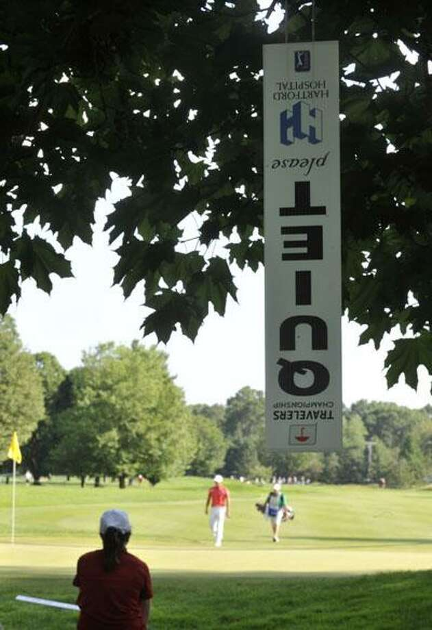A quiet sign hangs upside down in a tree as James Nittie approaches the seventh green during the second round of the Travelers Championship golf tournament on Friday. (AP) Photo: AP / AP2010