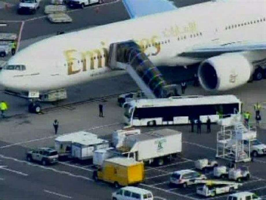 In this frame grab taken from WABC-TV video, passengers disembark an Emirates airliner into an awaiting bus at John F. Kennedy International Airport in New York, Friday Oct. 29, 2010, after having been escorted from the Canadian border to New York City by two military fighter jets. U.S. officials said there is no known threat associated with the plane, but it was being escorted to JFK as a precautionary move. Authorities on Friday were investigating whether suspicious packages shipped aboard cargo planes from Yemen to the U.S. were part of a terrorist plot. (AP Photo/WABC-TV) MANDATORY CREDIT Photo: AP / WABC TV
