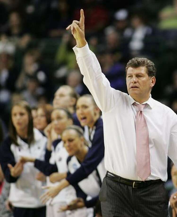 In this March 31, 2009 file photo, Connecticut coach Geno Auriemma signals to players as players on the bench cheer during the second half of an NCAA women's college basketball tournament regional final against Arizona State in Trenton, N.J. Connecticut will begin the season the same way it has the last two, atop The Associated Press women's basketball poll. The team won received 39 of the 40 first-place votes Friday. (AP) Photo: AP / FR125054 AP