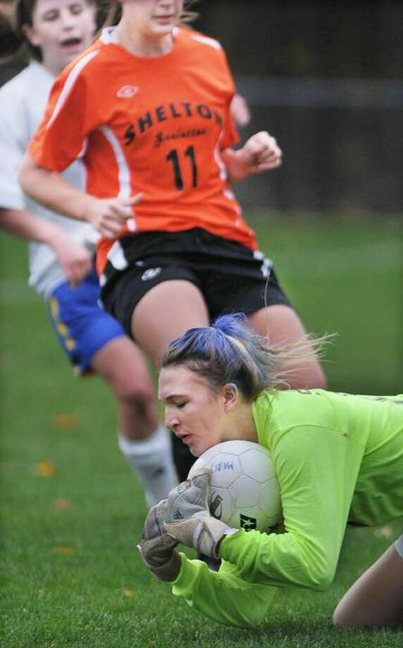 Mercy goalie, captain Katie Donnelly beats Shelton's Angela Ferro to the ball during senior night at Tiger Field in Middletown Friday. Shelton defeated Mercy 2-1. (Catherine Avalone / TheMiddletownPress