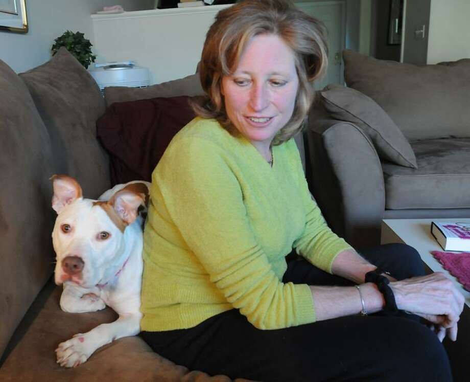 Diane Pearce at home in Hamden with Princess, a dog who has recovered from being stabbed 29 times by her previous owner. Mara Lavitt/Register