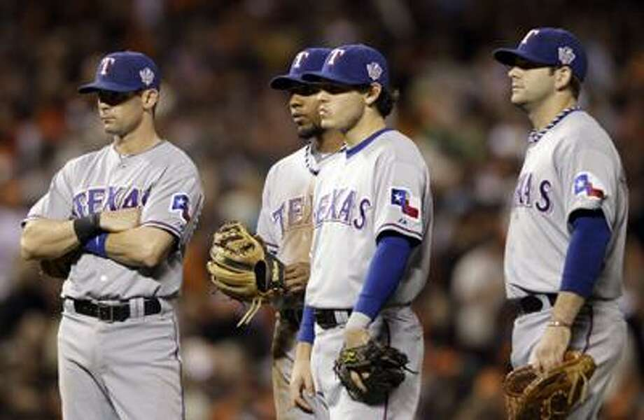 From left, Texas Rangers' Michael Young, Elvis Andrus, Ian Kinsler and Mitch Moreland wait for a pitcher change during the eighth inning of Game 2 of baseball's World Series against the San Francisco Giants Thursday. (AP) Photo: ASSOCIATED PRESS / AP