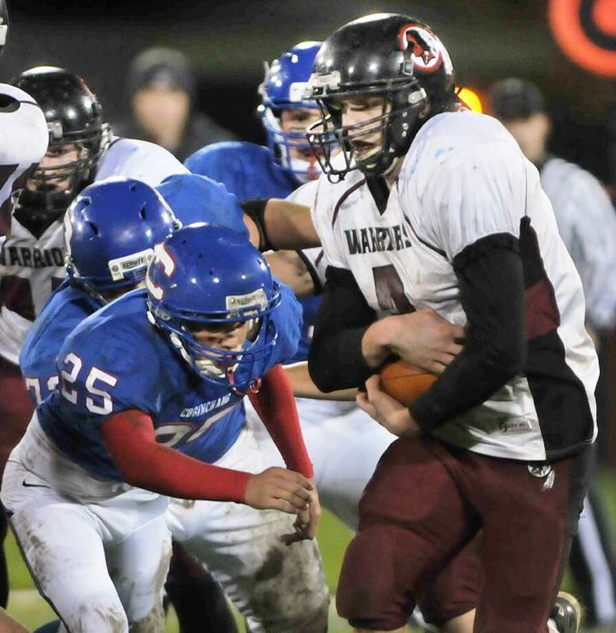 Coginchaug's Tanner Pedersen has his eyes on Valley Regional's Kyle Connor as he carries the ball during a Friday night homecoming game at Palmer Field in Middletown. (Catherine Avalone / TheMiddletownPress