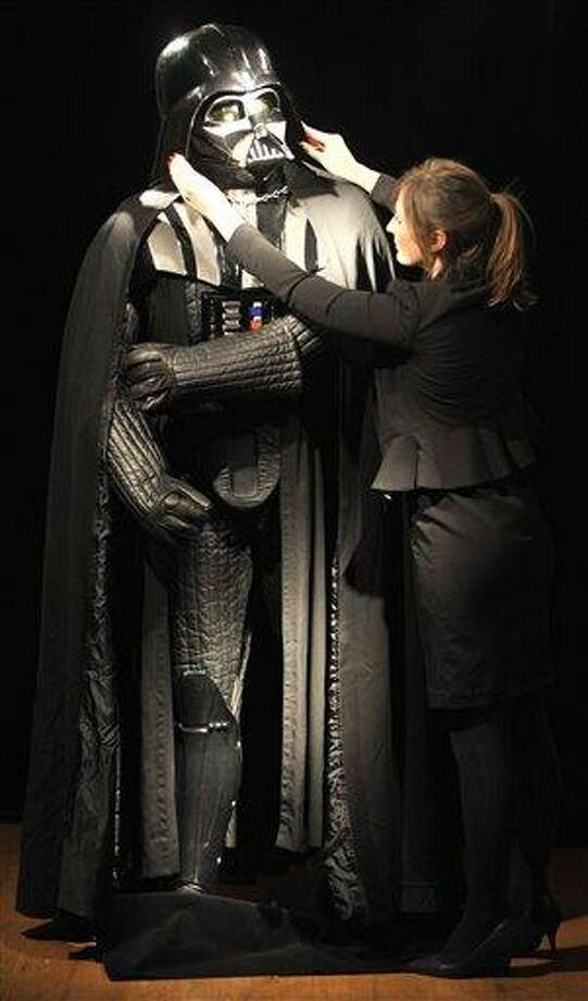 Christie's employee Caitlin Graham poses with a Darth Vader costume in London, Wednesday, Oct. 27, 2010. The helmet, mask, shoulder armour and shin guards of the costume have been produced for the second Star Wars movie 'The Empire Strikes Back', released in 1980. On November 25, 2010 the costume will be offered at Christie's South Kensington and is expected to realise 160,000 GBP to 230,000 GBP.(AP Photo/Lennart Preiss) Photo: AP / AP