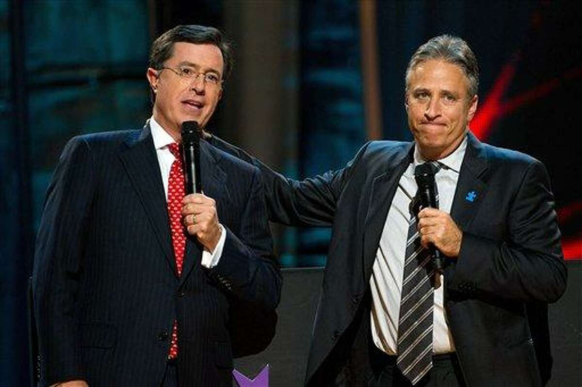 FILE - In this Oct. 2, 2010 file photo, Stephen Colbert, left, and Jon Stewart appear on stage at Comedy Central's 'Night Of Too Many Stars: An Overbooked Concert For Autism Education' at the Beacon Theatre in New York. (AP Photo/Charles Sykes)