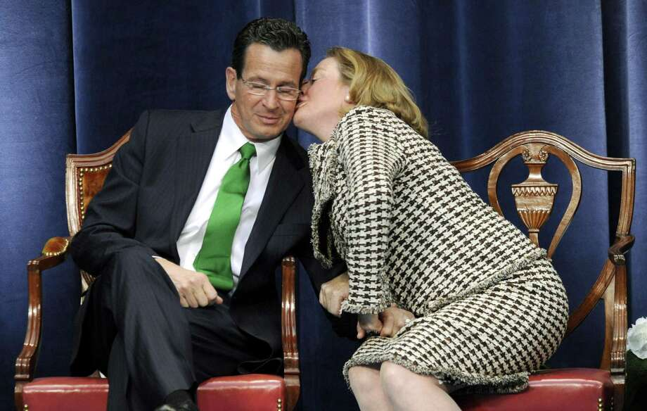 "In this Jan. 5, 2011 file photo, Gov. Daniel P. Malloy gets a kiss from his wife Cathy while ""Danny Boy"" is played during his inauguration ceremony in Hartford Conn. The new first lady said Thursday, that she'll remain at her job as executive director of the Sexual Assault Crisis and Education Center in Stamford,  but is looking for a new job in the Hartford area. (AP Photo/Sean D. Elliot, Pool, File) Photo: AP / AP2011"