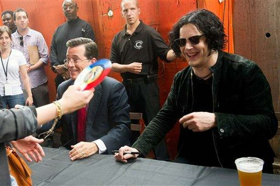 "Stephen Colbert, left, and Jack White sign copies of their vinyl record, ""Charlene II (I'm Over You),""  in New York, Friday. Colbert debuted his new Jack White-produced single on ""The Colbert Report"" on Thursday night. (AP Photo/Charles Sykes) Photo: AP / FR170266 AP"