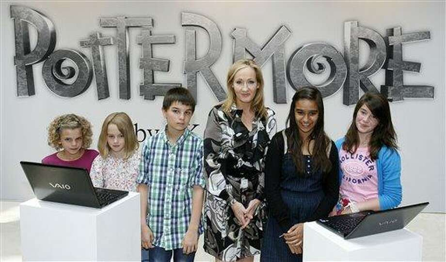 British author J.K. Rowling, third right, poses for photographers with children as she announces her new website project 'Pottermore' at the Victoria and Albert Museum in London, Thursday. For the project she has written new material about the characters, places and objects in the Harry Potter stories. (AP Photo/Akira Suemori) Photo: AP / AP