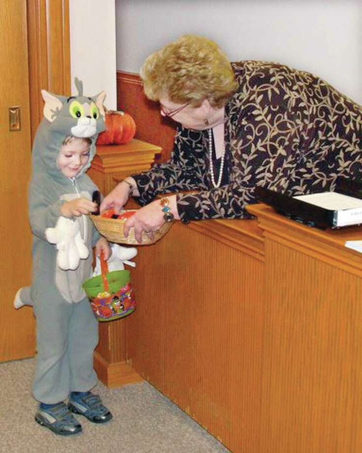 Photo courtesy Marcia Pendleton-Sacco  10.25.10   Three year old, Liam Walsh, of Cromwell gets candy from Re Matus, the secretary for Cromwell's First Selectman at Town Hall Pre-Halloween' Playtime, Party and Trick or Treat sponsored by the Cromwell Youth Services.