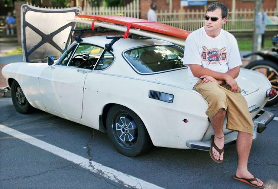 """Alex Yoknat of Essex sits on the back of his 1971 Volvo P-180 E at the 13th Annual Cruise Night on Main Street. Yoknat has had the car for 13 years and drives it daily. Roger More drove the same car in the 1960s telivisions show """"The Saint."""" (Andrew Phillip Avalone"""