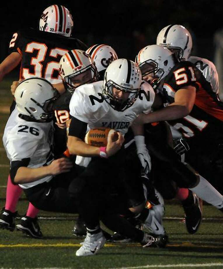 Pictured from left to right Xavier's 26 Mike Mastrioanni (26), Shelton's Jagger Kalagian (12), Xavier quarterback Pat D'Amato (2) and Shelton's Robert Rose (51). Photo by Mara Lavitt/New Haven Register  10/21/11