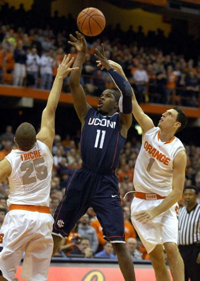 Connecticut's Jerome Dyson, center, has his shot tipped by Syracuse's Andy Rautins, right, as Brandon Triche defends during the first half of Wednesday's game. (Associated Press) Photo: AP / FR60349 AP