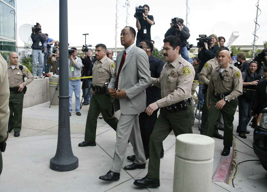 Conrad Murray, Michael Jackson's doctor, center, is escorted by Los Angeles County Sheriffs deputies as he arrives at the Airport Courthouse to face charges of involuntary manslaughter in the singer's death in Los Angeles on Monday. (AP) Photo: AP / FR74394 AP