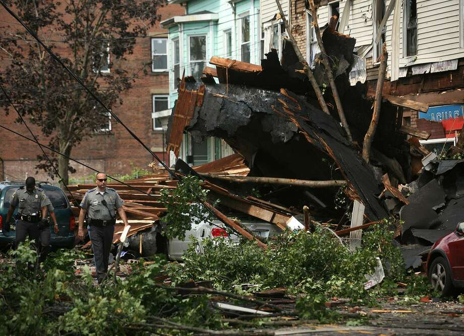 The roof of a building crashed down upon cars during a violent thunderstorm today in Bridgeport. A suspected tornado tore through Connecticut's largest city Thursday -- a rare occurrence in the state -- toppling trees and power lines and collapsing a building as a powerful line of storms swept across parts of the Northeast. Remarkably, no serious injuries were reported. (AP) Photo: AP / Connecticut Post
