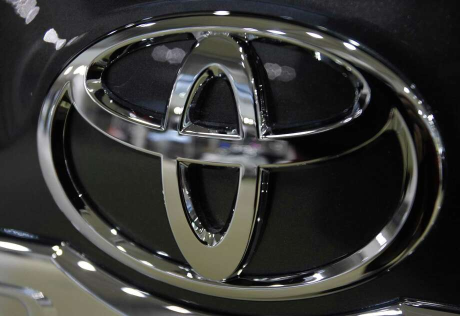 In this Jan. 26, 2011 photo, the logo of Toyota Motor Corp. shines in front of a car displayed at the Japanese automaker's showroom in Tokyo. Toyota Motor Corp. is recalling 2.17 million vehicles in the United States to address accelerator pedals that could become entrapped in floor mats or jammed in carpeting. (AP Photo/Shizuo Kambayashi, file) Photo: ASSOCIATED PRESS / AP2011