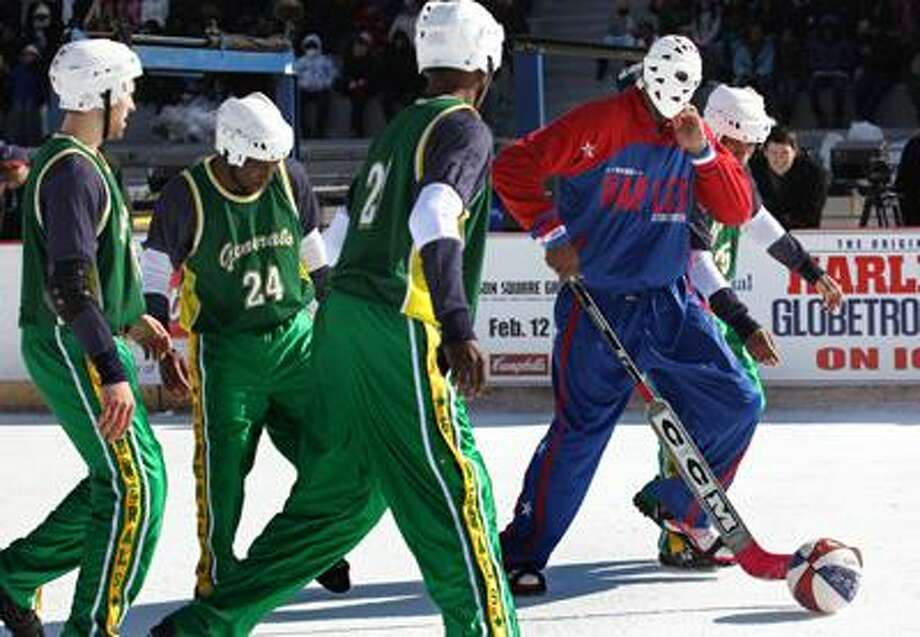 Kris Hi-Lite Bruton, right, of the Harlem Globetrotters moves the ball with a goalie stick as his team took on the Washington Generals during a basketball game on the outdoor ice rink at Lasker Rink in New York's Central Park on Tuesday. (Associated Press) Photo: ASSOCIATED PRESS / AP2010